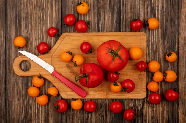 Draufsicht der frischen orange und roten tomaten lokalisiert auf einem hölzernen küchenbrett mit messer auf einer holzwand