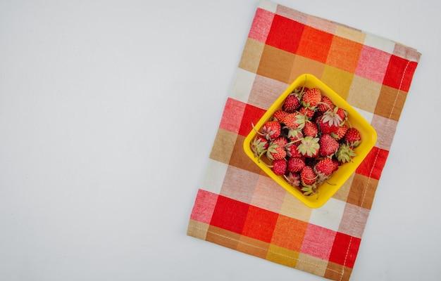 Draufsicht der frischen reifen erdbeeren in der gelben schüssel auf karierter serviette auf weiß mit kopienraum