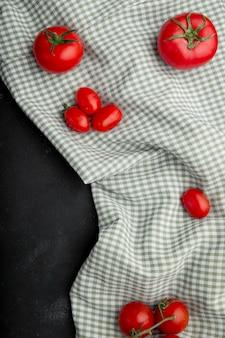 Draufsicht der frischen reifen roten tomaten auf karierter tischdecke auf schwarzem hintergrund
