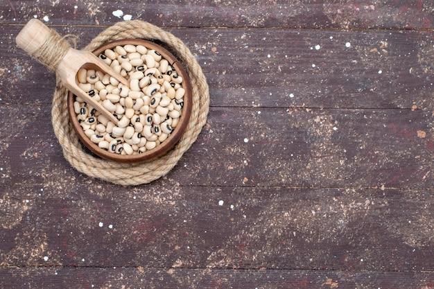 Draufsicht der frischen rohen bohnen innerhalb der braunen schüssel auf braunem rustikalem holz, roher bohnenharicot des lebensmittels