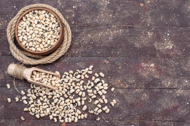 Draufsicht der frischen rohen bohnen innerhalb der braunen schüssel mit seil auf braunem schreibtisch, lebensmittel rohe bohnenharicot