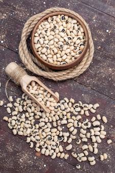 Draufsicht der frischen rohen bohnen innerhalb der braunen schüssel mit seil auf brauner, roher bohnen-haricot des lebensmittels