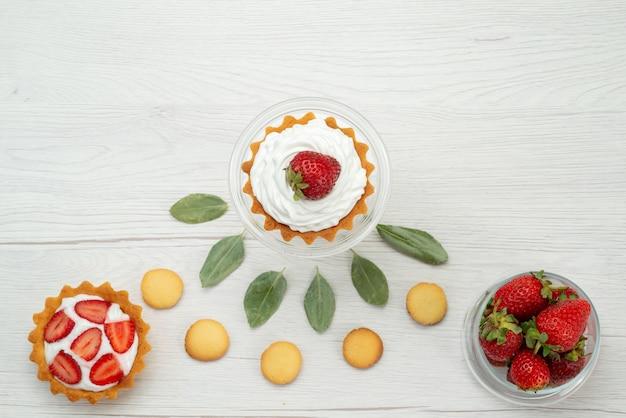 Draufsicht der frischen roten erdbeeren weich und köstliche beeren mit kuchen und keksen auf hellem schreibtisch, fruchtbeere frisch