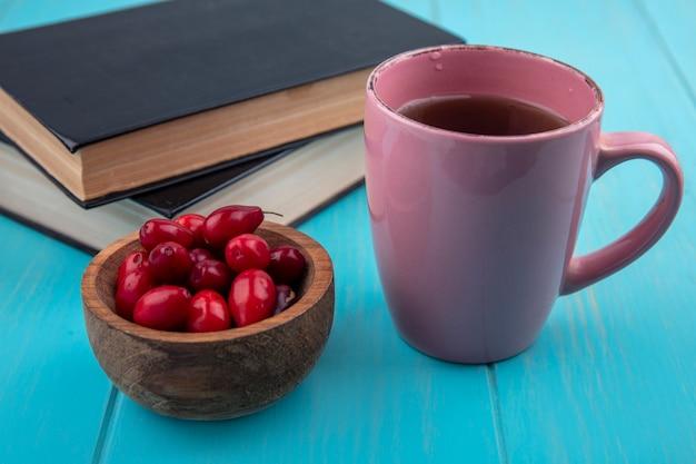 Draufsicht der frischen roten kornelkirschenbeeren auf einer hölzernen schüssel mit einer tasse tee auf einem blauen hölzernen hintergrund