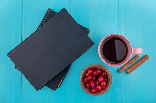 Draufsicht der frischen roten kornelkirschenbeeren auf einer hölzernen schüssel mit einer tasse tee und zimtstangen auf einem blauen hölzernen hintergrund
