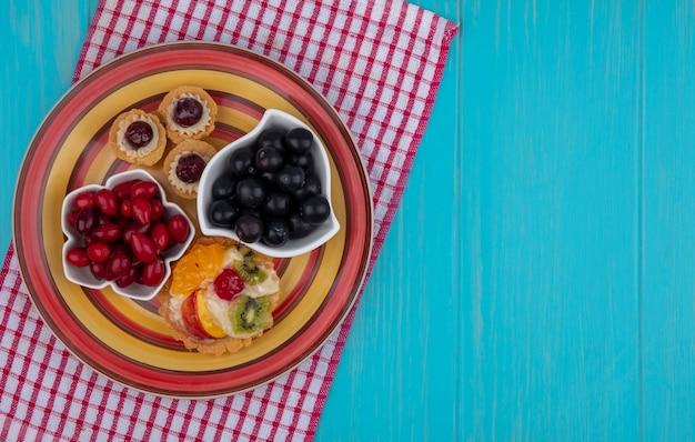 Draufsicht der frischen roten kornelkirschenbeeren auf einer schüssel mit trauben und torten auf einem roten karierten tuch auf einem blauen hölzernen hintergrund mit kopienraum