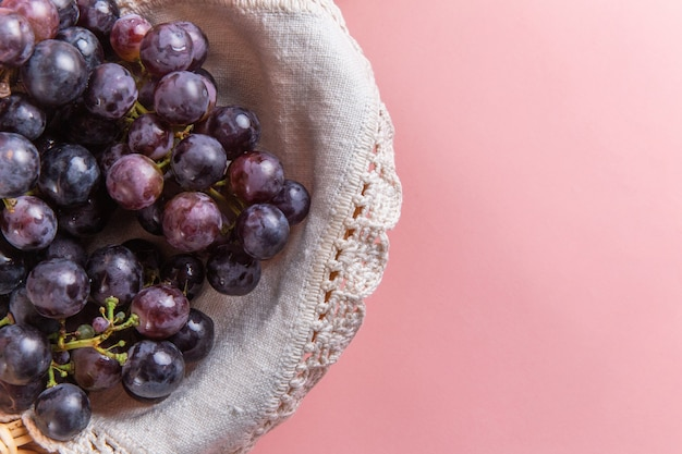 Draufsicht der frischen sauren trauben im korb auf rosa oberfläche