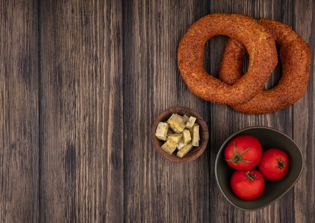 Draufsicht der frischen türkischen bagels mit gehackten scheiben des käses und der tomaten auf einer schüssel auf einem hölzernen hintergrund mit kopienraum