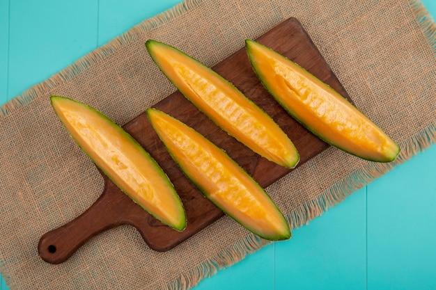 Draufsicht der frischen und gesunden melone melone auf holz küchenbrett auf sack stoff auf blau