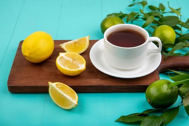 Draufsicht der frischen zitronen auf holzküchenbrett mit einer tasse tee auf blau