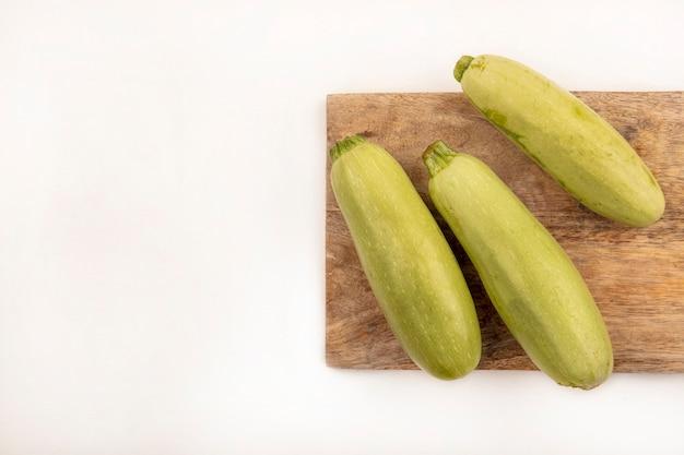 Draufsicht der frischen zucchini lokalisiert auf einem hölzernen küchenbrett auf einer weißen oberfläche mit kopienraum