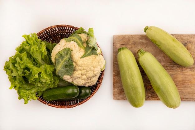 Draufsicht der frischen zucchini lokalisiert auf einem hölzernen küchenbrett mit blumenkohlsalat und gurken auf einem eimer auf einer weißen wand