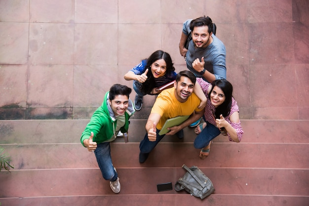 Draufsicht der fröhlichen indischen asiatischen jungen gruppe von college-studenten oder freunden, die zusammen auf dem campus stehen