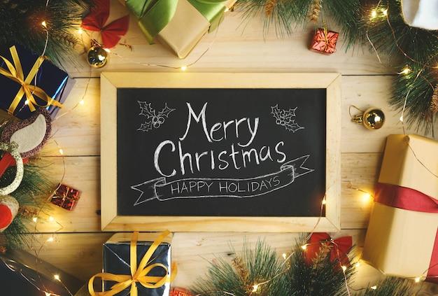 Draufsicht der frohen weihnachtstypografie auf der tafel umgeben durch weihnachtsgeschenk-verzierung