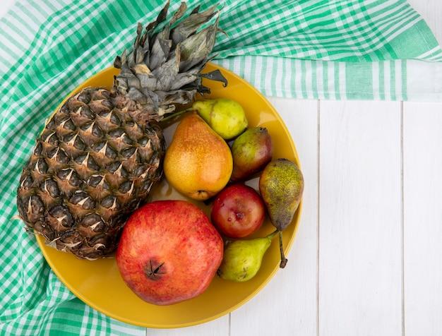 Draufsicht der früchte als ananas, birnen, granatapfel und pfirsich in platte auf kariertem stoff auf holzoberfläche mit kopierraum