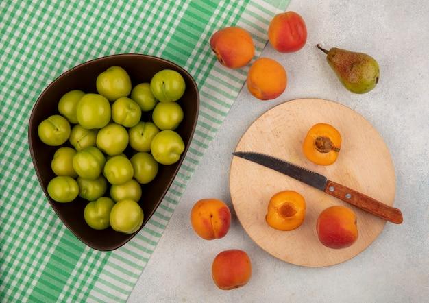 Draufsicht der früchte als ganze und halb geschnittene aprikose mit messer auf schneidebrett und pflaumenschale auf kariertem stoff mit aprikosen und birne auf weißem hintergrund