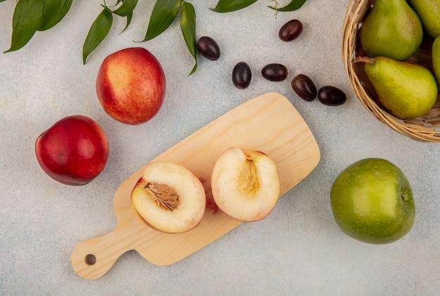 Draufsicht der früchte als halb geschnittener pfirsich auf schneidebrett und birnenschale mit traubenbeerenapfel mit blättern auf weißem hintergrund