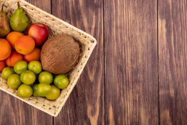 Draufsicht der früchte als kokosnusspflaumen-aprikosenpfirsichbirne im korb auf hölzernem hintergrund mit kopienraum