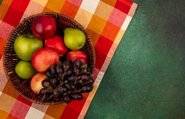 Draufsicht der früchte als pfirsich-apfel-birnen-traube im korb auf kariertem stoff und auf grünem hintergrund mit kopienraum