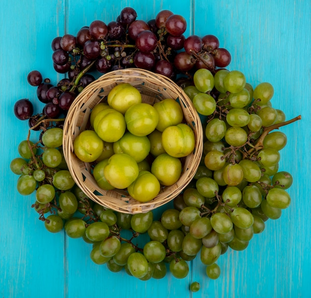 Draufsicht der früchte als pflaumen im korb und in den trauben herum auf blauem hintergrund