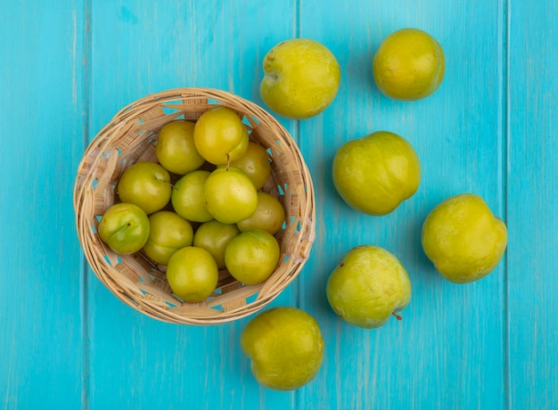 Draufsicht der früchte als pflaumen im korb und muster der grünen pluots auf blauem hintergrund