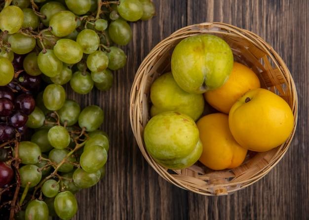 Draufsicht der früchte als pluots und nectacots im korb und in den trauben auf hölzernem hintergrund