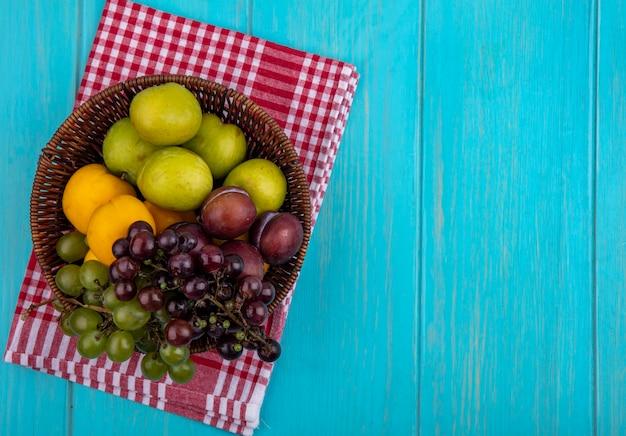 Draufsicht der früchte als trauben pluots nectacots im korb auf kariertem stoff und blauem hintergrund mit kopienraum