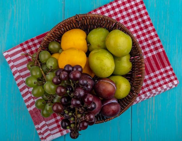 Draufsicht der früchte als trauben pluots nectacots im korb auf kariertem stoff und blauem hintergrund