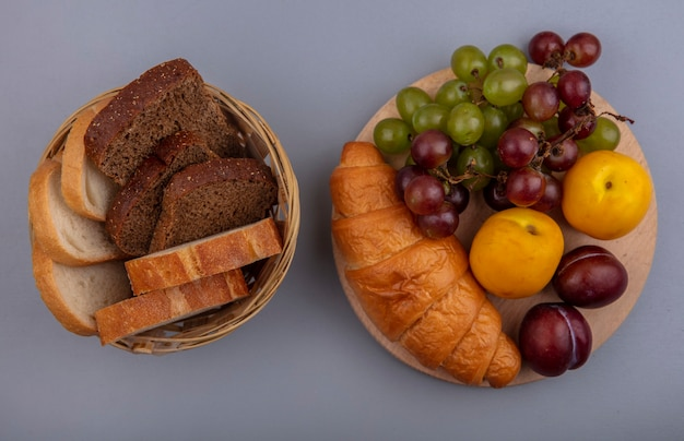 Draufsicht der früchte als traubennektakot und pluot mit croissant auf schneidebrett und brotkorb auf grauem hintergrund