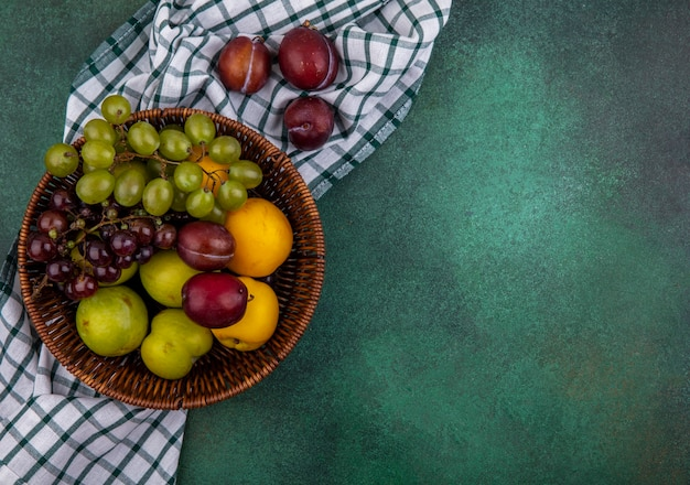 Draufsicht der früchte als traubenpluots und -nektakots im korb auf kariertem stoff auf grünem hintergrund mit kopienraum