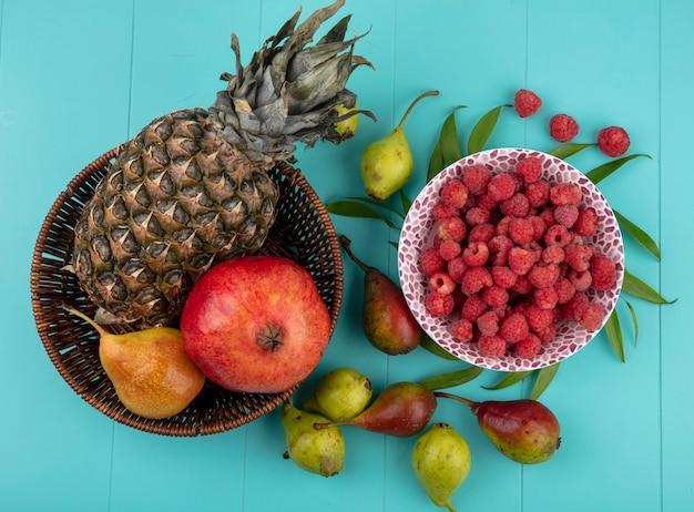 Draufsicht der früchte im korb und in der schüssel der himbeere mit pfirsichen und blättern auf blauer oberfläche