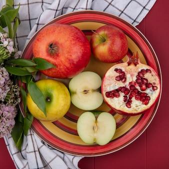 Draufsicht der früchte im teller und in den blumen auf kariertem stoff auf roter oberfläche