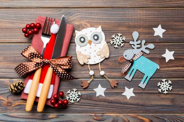 Draufsicht der gabel und des messers auf serviette. verschiedene weihnachtsschmuck und spielzeug. schließen sie oben vom abendessenkonzept des neuen jahres