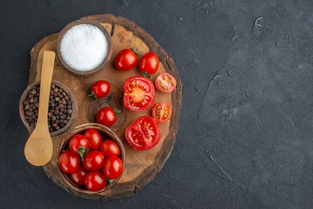 Draufsicht der ganzen geschnittenen frischen tomaten und des pfeffers auf holzbrett auf schwarzer oberfläche
