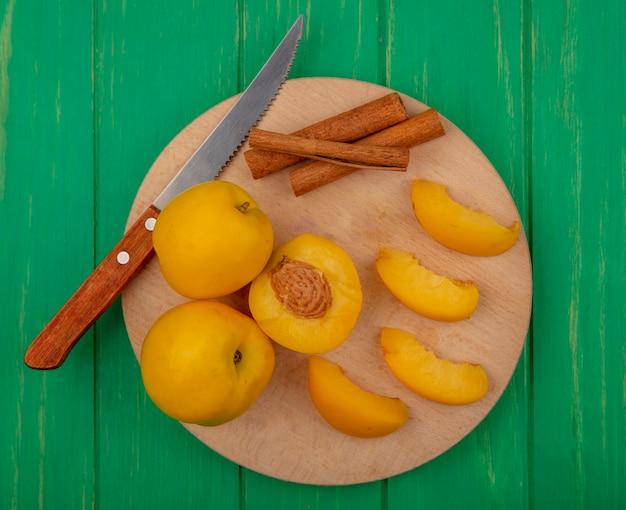 Draufsicht der ganzen geschnittenen und geschnittenen aprikosen mit zimt und messer auf schneidebrett auf grünem hintergrund