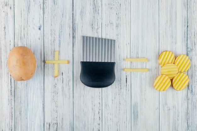 Draufsicht der ganzen und geschnittenen kartoffel mit kartoffelschneider auf hölzernem hintergrund mit kopienraum Kostenlose Fotos