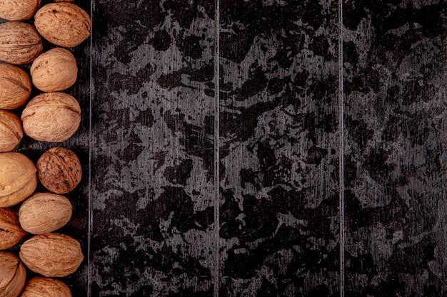 Draufsicht der ganzen walnüsse auf schwarzem hölzernem hintergrund mit kopienraum