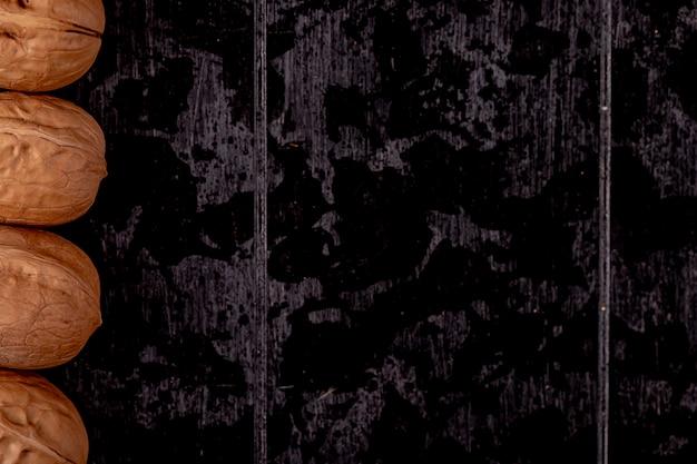 Draufsicht der ganzen walnüsse, die in einer reihe auf schwarzem hölzernem hintergrund mit kopienraum ausgekleidet sind