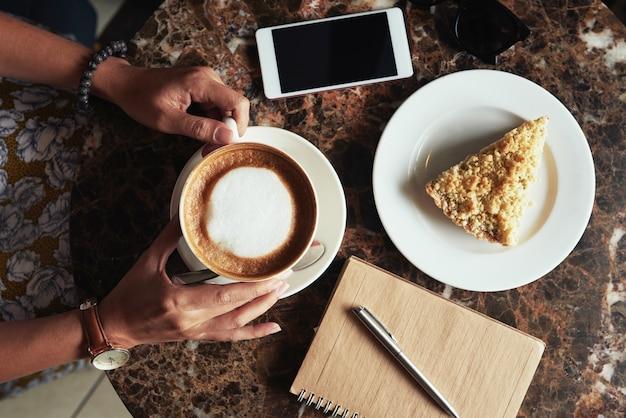 Draufsicht der geernteten unerkennbaren frau, die kaffee und nachtisch im café trinkt
