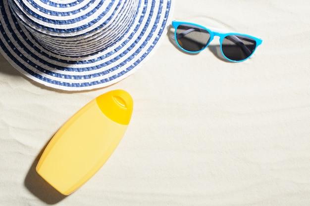 Draufsicht der gelben cremeflasche auf sand mit hut und blauer sonnenbrille