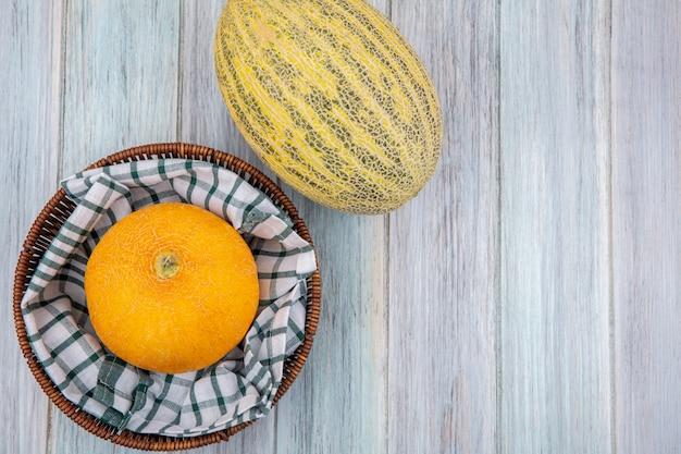 Draufsicht der gelben melone auf einer karierten tischdecke auf einem eimer auf grauer holzoberfläche