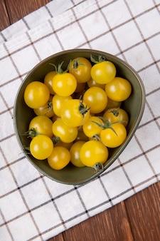 Draufsicht der gelben tomaten in der schüssel auf stoff und holztisch