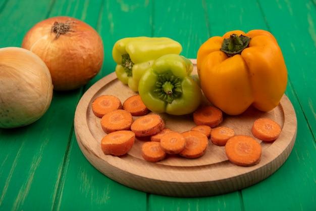 Draufsicht der gelben und grünen paprika auf einem hölzernen küchenbrett mit gehackten karotten mit zwiebeln, die auf einer grünen holzwand lokalisiert werden