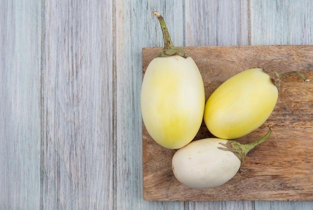 Draufsicht der gelben und weißen auberginen auf schneidebrett auf hölzernem hintergrund mit kopienraum
