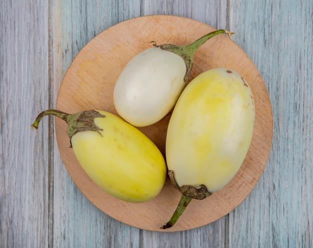 Draufsicht der gelben und weißen auberginen auf schneidebrett auf hölzernem hintergrund