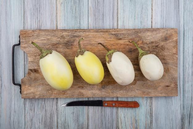 Draufsicht der gelben und weißen auberginen auf schneidebrett mit messer auf hölzernem hintergrund