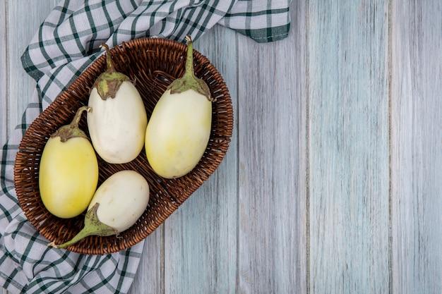 Draufsicht der gelben und weißen auberginen im korb auf kariertem stoff auf hölzernem hintergrund mit kopienraum