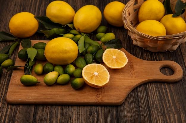 Draufsicht der gelben zitronen auf einem eimer mit zitronen und kinkans auf einem hölzernen küchenbrett auf einer hölzernen oberfläche