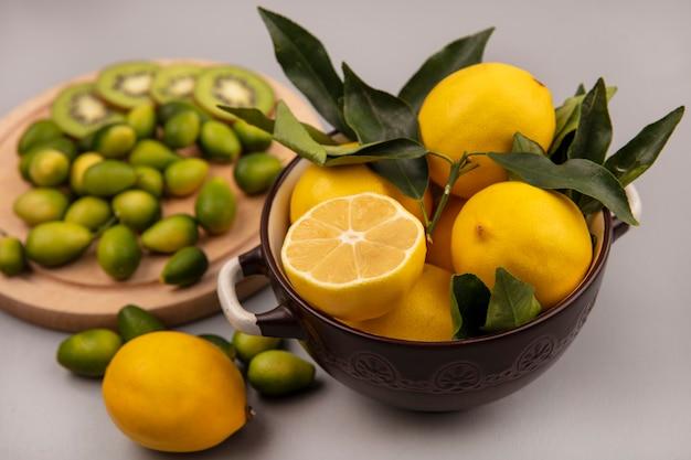 Draufsicht der gelben zitronen auf einer schüssel mit kinkans und kiwischeiben auf einem hölzernen küchenbrett auf einer weißen wand