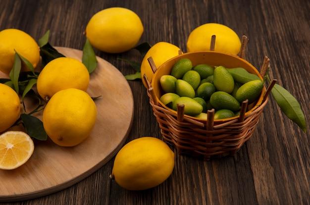 Draufsicht der gelbhäutigen zitronen lokalisiert auf einem hölzernen küchenbrett mit kinkans auf einem eimer auf einer holzwand